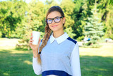Beautiful young woman walking in the park. Woman in glasses is drinking coffee.