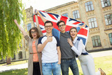 Group of students holding a flag of Great Britain on the university campus background. - 175604198