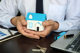 Real estate marketing. Agent holding model of house.