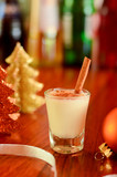 Chirstmas hot drink eggnog in a glas with a golden decoration stuff - 175624728
