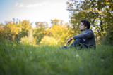 Junger Mann sitzt im Gras, entspannt und nachdenklich, Textfreiraum - 175625991