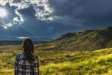 woman looks out toward stunning views of sun bursting through clouds over a mountain range