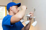 electrician at work - installing lamp on the wall - 175627304