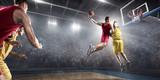 Koszykarz robi slam dunk na dużej profesjonalnej arenie. Gracz leci w powietrzu z piłką. Przeciwnicy próbują zapobiec uderzeniu piłki w pierścień do koszykówki.