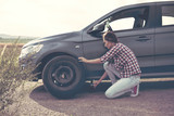 .Beautiful young woman changing tires on her car - 175631937