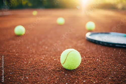 Tennis balls and racket on tennis court