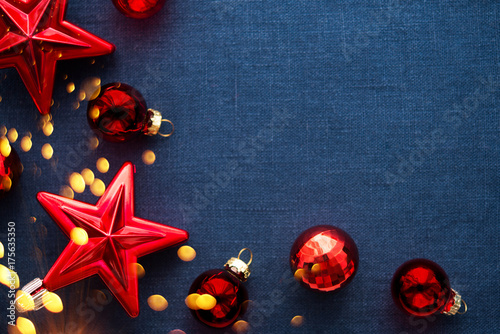 Christmas background with red ornaments and sparkle bokeh lights on blue canvas background. Merry christmas greeting card, banner. Winter holiday xmas theme. Happy New Year.