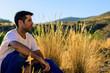 Joven mirando al horizonte en el campo con huerbas altas