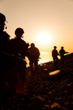 Army soldiers with rifles orange sunset silhouette - 175663134