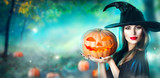 Halloween witch with a carved pumpkin and magic lights in a dark forest - 175673396
