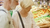 Senior couple shopping in grocery store. Standing in vegetable department choosing fresh roots for salad. Veggies on background - 175677361