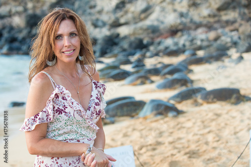 Beautiful woman near a large group of green sea turtles Poster