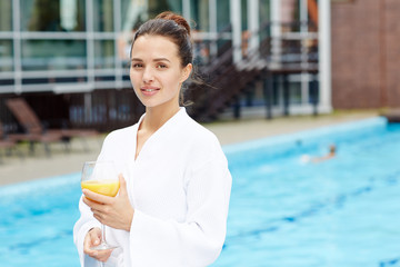 Carefree young female in bathrobe standing by swimming pool by hotel © pressmaster