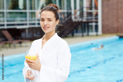 Carefree young female in bathrobe standing by swimming pool by hotel