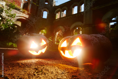 Evil grins of jack-o-lanterns burning on halloween night - 175688712