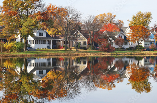 Autumn in a city background. Fall cityscape with private houses neighborhood along a pond. Colorful trees and houses reflected in a water. Midwest USA, Wisconsin. Classic american middle class homes. - 175692950