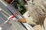 Femme peint un volet - 175695195