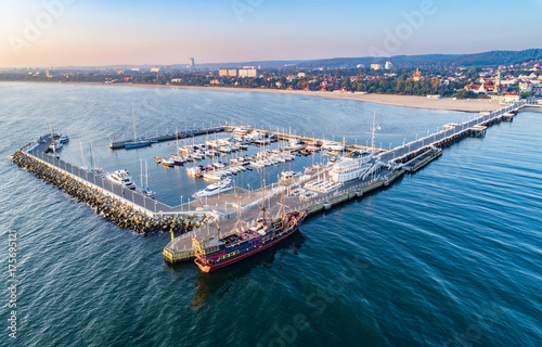 Sopot resort in Poland. Wooden pier (molo) with marina, yachts, pirate tourist ship, beach and vacation infrastructure. Aerial view at sunrise