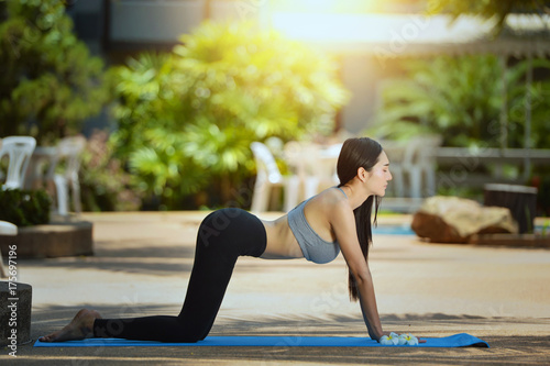 Plakat woman is practicing yoga at garden,Woman Yoga - relax in nature,Young woman doing yoga in morning park