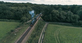 Aerial view of an old fashioned steam train crossing the English countryside - 175725764