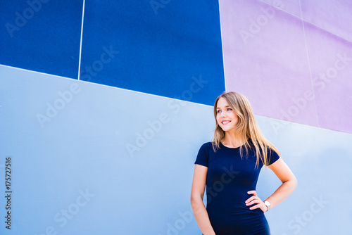 Happy beautiful young woman posing by a colorful wall Poster