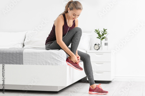 Young sporty woman with phone tying shoelaces at home - 175729143