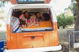 Happy young friends lying in camper van - 175736511