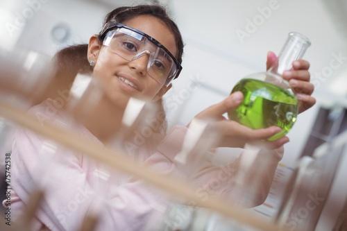 Portrait of elementary student holding green chemical in beaker