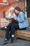 two friends reading a book - 175747784