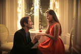 Handsome man proposing a beautiful woman to marry him in an elegant restaurant - 175748719
