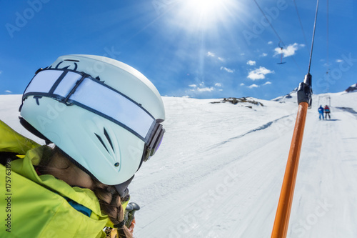 Happy young woman skier on ski drag lift.