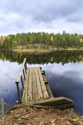 Fotobehang Bruggen Old wooden bridge in a lake in autumn