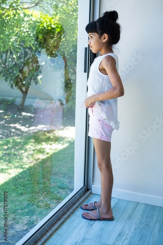 Side view of girl looking through window - 175780192