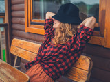 Woman with hat relaxing on porch - 175800156