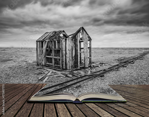 Foto op Aluminium Donkergrijs Derelict fishing hut and rails on shingle beach during stormy Winter landscape concept coming out of pages in open book