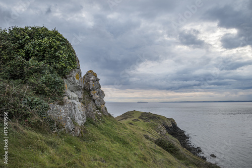 Fotobehang Landschappen Looking out to sea at stormy dramatic sky over landscape