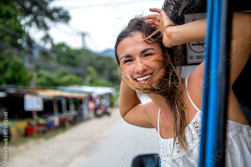smiling girl looks out of the window of a taxi, tuk-Tuk Poster