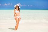 Attractive young woman enjoys Maldivian beach walking in the ocean water - 175819133
