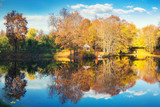 Sunny autumn landscape with blue sky over lake - 175819520