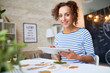 Portrait of happy young woman using digital tablet and smiling looking at camera while making handmade Autumn decorations at home
