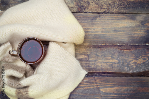 Papiers peints The Cup of hot tea wrapped warm woolen scarf on a wooden background. Mock up