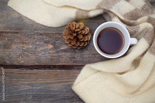 Papiers peints The A cup of hot tea and a warm scarf on a wooden background. Flat lay