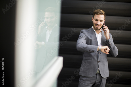 Businessman using mobile phone and looking on the watch