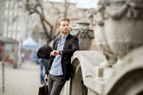 Caucasian businessman waiting outside and looking at his watch.