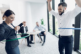 Fun in the office. A man and a woman twist hula hoops. Two of their colleagues sit at the table and look at them. - 175840343