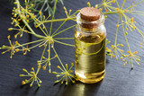 A bottle of dill seed oil on a dark background - 175840562