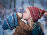 A little girl kisses a Teddy bear. snowing, winter - 175840594