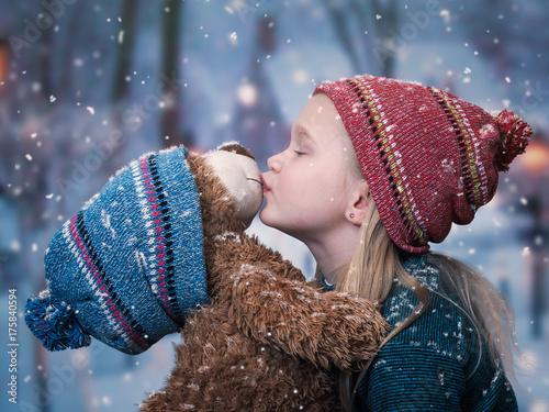 A little girl kisses a Teddy bear. snowing, winter