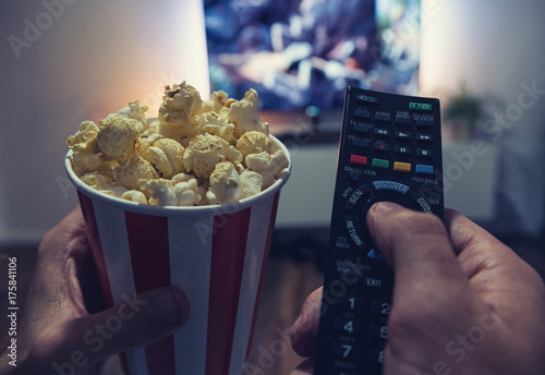 Poster young man Watching a Movie in his living room with popcorn and remote control, P