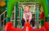 Girl of three-years comes down from the slide on the playground in the park. - 175845510